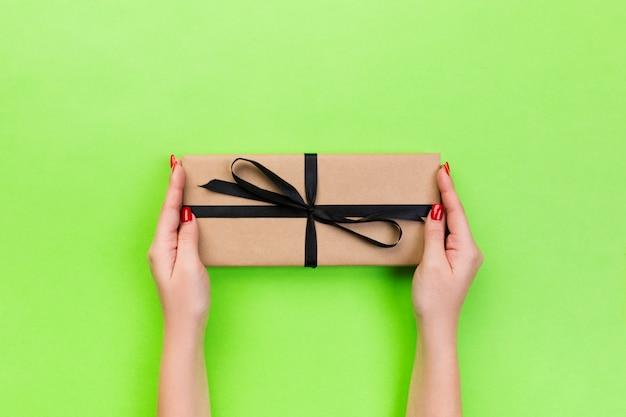 Ręce kobiety dają zapakowane walentynki lub inne ręcznie robione prezenty w papierze z czarną wstążką. pudełko, dekoracja prezentu na zielonym stole, widok z góry z miejsca kopiowania Premium Zdjęcia
