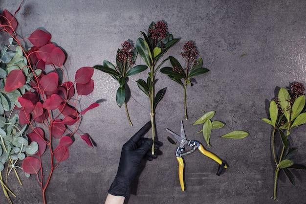 Ręce kwiaciarni i różne piękne kwiaty leżą na szarym stole. Premium Zdjęcia