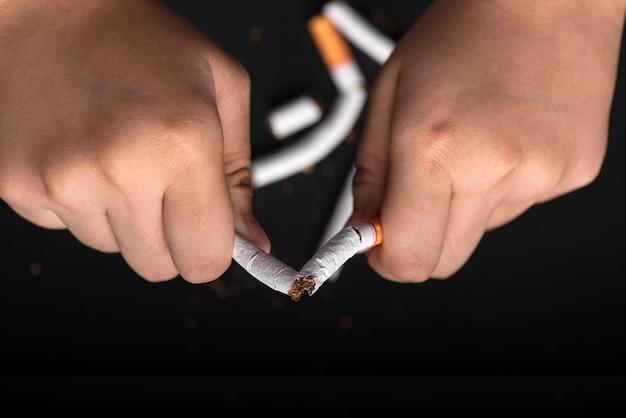 Ręce łamiące papierosa na rzucenie dymu Premium Zdjęcia