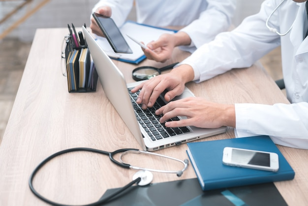 Ręce lekarzy, którzy siedzą przed komputerem. Premium Zdjęcia