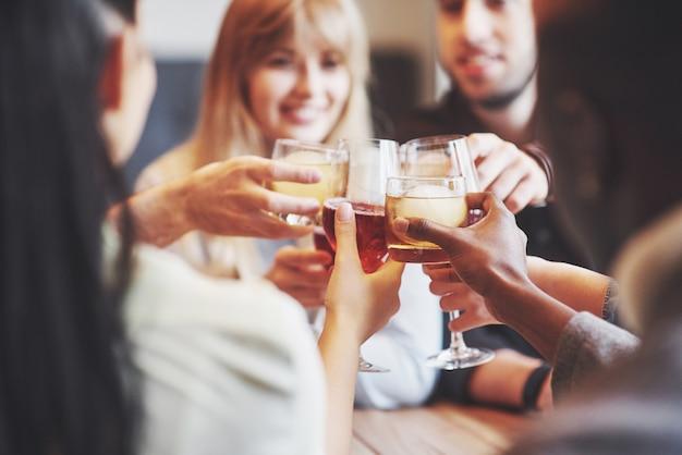 Ręce ludzi w szklankach whisky lub wina, świętujących i opiekających Premium Zdjęcia