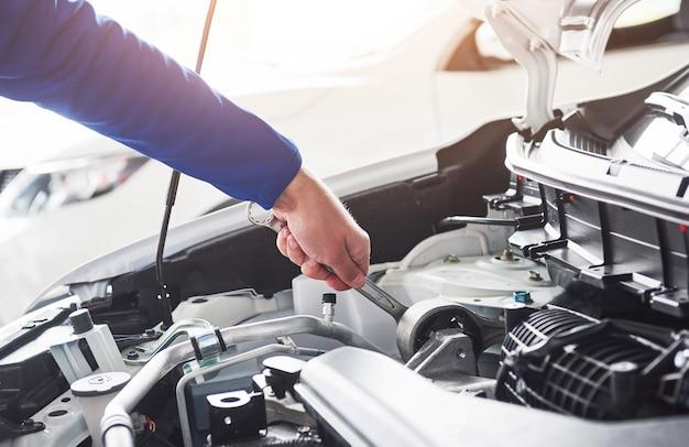 Ręce Mechanika Samochodowego Z Kluczem W Garażu Premium Zdjęcia