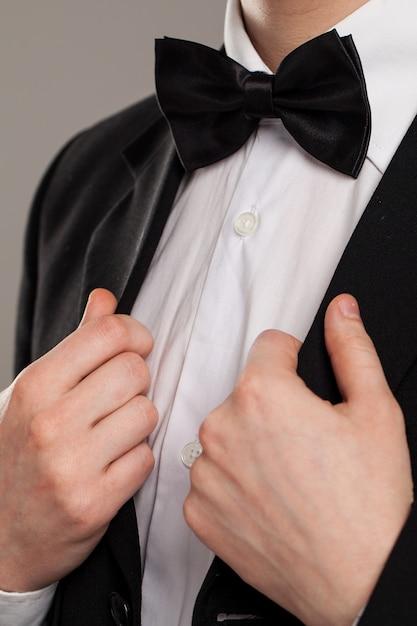 Ręce mężczyzny dotykają muszki Darmowe Zdjęcia