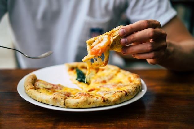 Ręce mężczyzny trzymają pizzę Darmowe Zdjęcia