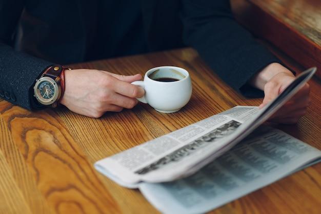 Ręce Mężczyzny Z Bliska Trzymając Filiżankę Kawy I Gazety Darmowe Zdjęcia