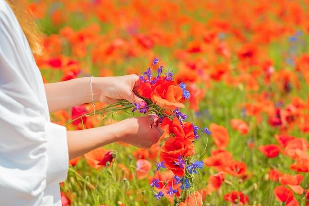 Ręce Młodej Pięknej Kobiety Tka Wieniec Z Kwiatów Maku W Polu Latem Darmowe Zdjęcia