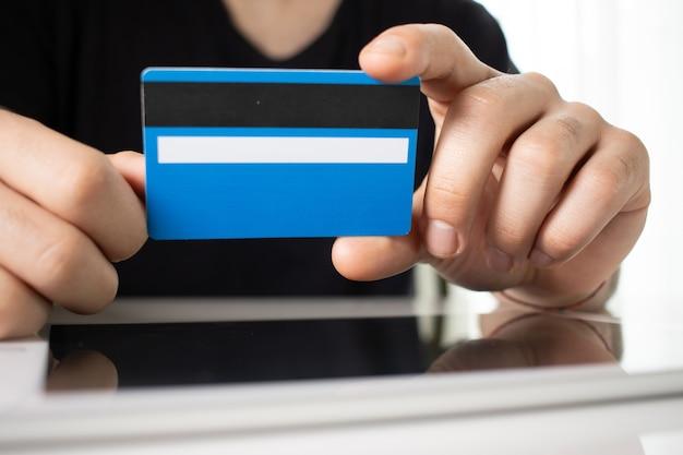 Ręce Osoby Trzymającej Niebieską Kartę Kredytową Na Odbijającej Powierzchni W Białym Pokoju Darmowe Zdjęcia