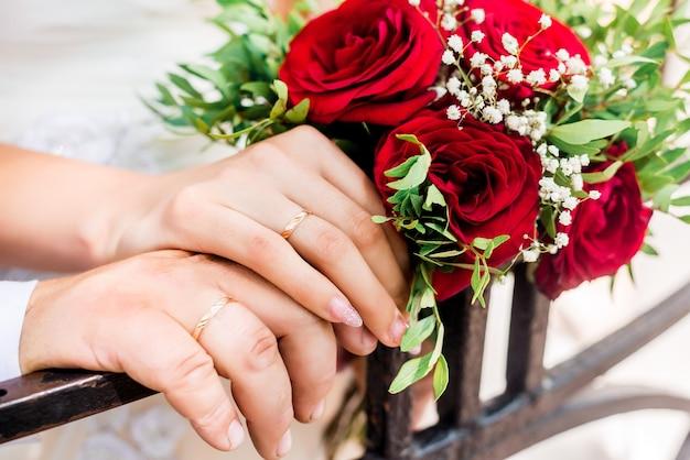 Ręce Panny Młodej I Pana Młodego Z Pierścieniami Na Bukiet ślubny. Koncepcja Małżeństwa. Premium Zdjęcia