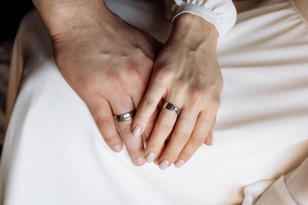 Ręce panny młodej i pana młodego z złote obrączki ślubne. ślub Premium Zdjęcia