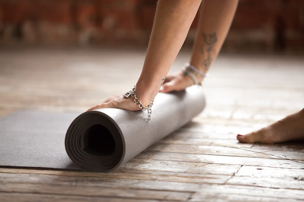 Ręce toczenia mata fitness. pojęcie zdrowego stylu życia Darmowe Zdjęcia