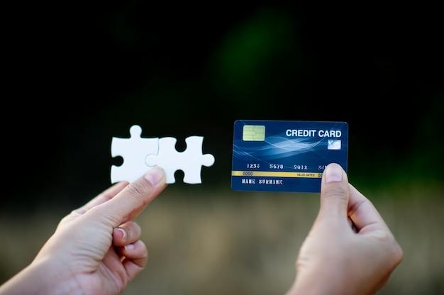Ręce Trzyma Białe Kawałki Układanki I Karty Kredytowej Premium Zdjęcia