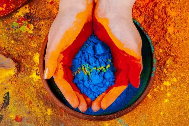 Ręce trzyma farbę proszkową holi, widok z góry Premium Zdjęcia