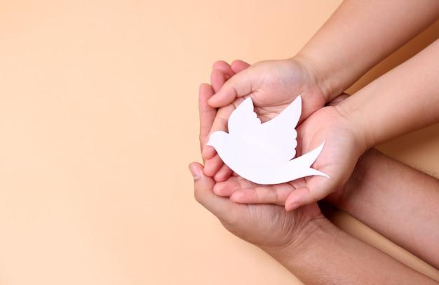 Ręce Trzymając Papier Biały Ptak, Koncepcja światowego Dnia Pokoju. Premium Zdjęcia