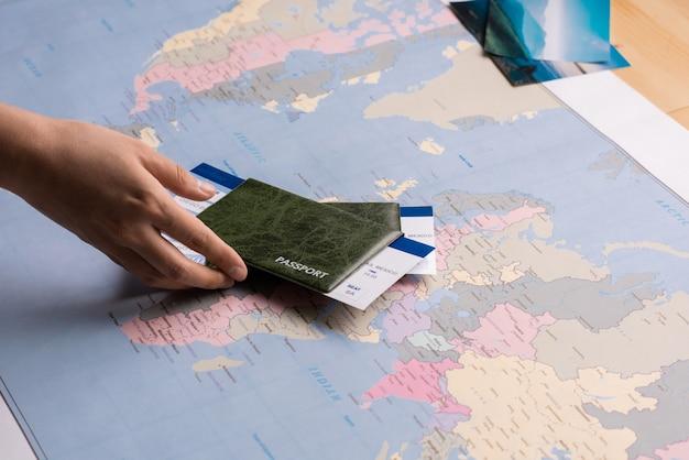 Ręce Umieszczając Paszporty Z Biletami Na Mapie świata Podczas Przygotowań Do Podróży Premium Zdjęcia
