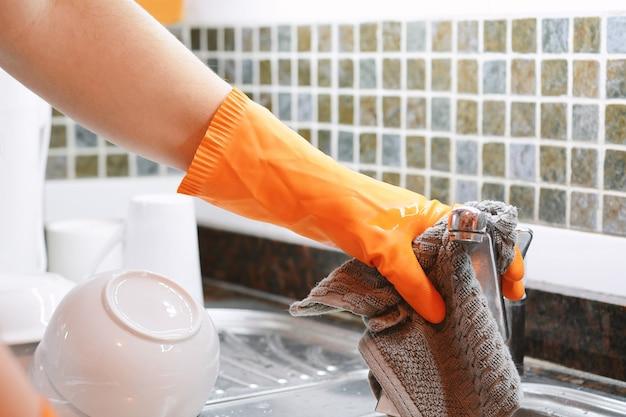 Ręce w gumowych rękawiczkach zmywa naczynia ze spon Premium Zdjęcia