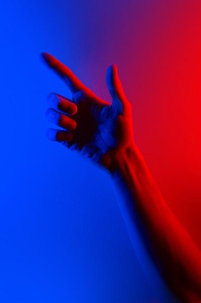 Ręce w kolorowe, niebieskie, czerwone światło neonowe. Premium Zdjęcia