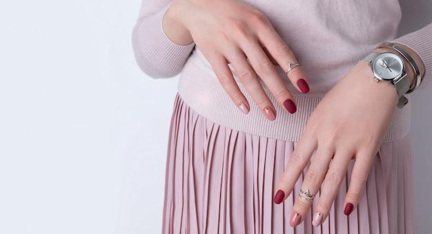 Ręce Womans Ze Srebrną Biżuterią I Akcesoriami. Dziewczyna Z Minimalistycznym Wzorem Różowego Wiosennego Lata Manicure. Premium Zdjęcia