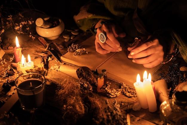 Ręce Wróżki Nad Starożytnym Stołem Z Ziołami I Książkami. Manifestacja Okultyzmu W Formie Wróżbiarstwa. Premium Zdjęcia