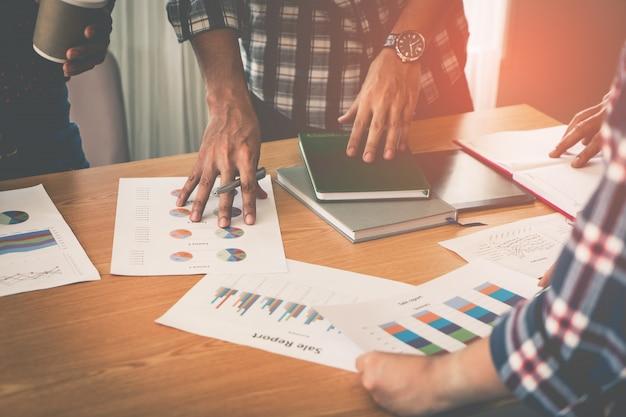 Ręce wskazując na arkuszu danych wykresu na spotkanie biznesowe Premium Zdjęcia