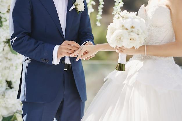 Ręce Z Obrączki. Modny Pan Młody Nakłada Złoty Palec Na Palec Panny Młodej Podczas Ceremonii ślubnej. Kochająca Para, Kobieta W Sukni ślubnej I Przystojny Mężczyzna W Stylowym Niebieskim Garniturze Premium Zdjęcia