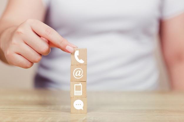 Ręczne układanie klocków drewnianych z ikoną telefonu, poczty, adresu i telefonu komórkowego Premium Zdjęcia