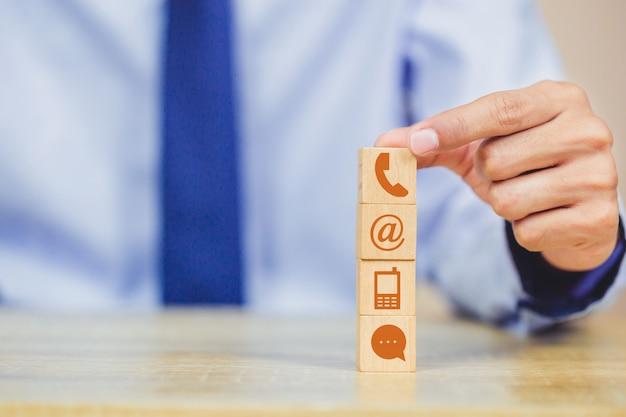 Ręczne układanie klocków drewnianych za pomocą telefonu, poczty, adresu i telefonu komórkowego iconl Premium Zdjęcia