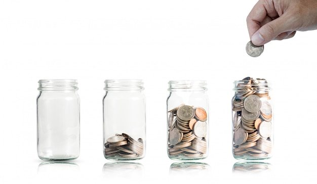 Ręczne wkładanie monet do słoika dla oszczędności i inwestycji. Premium Zdjęcia