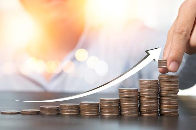 Ręczne Wprowadzenie Monet Sztaplowania Z Rosnącą Strzałką. Różnorodność Koncepcji Depozytów Bankowych I Inwestycji Giełdowych. Premium Zdjęcia