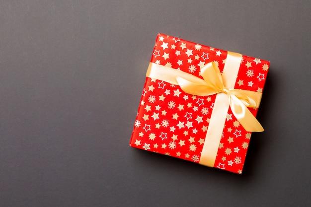 Ręcznie owinięty świąteczny prezent w papier ze złotą wstążką na czarno Premium Zdjęcia