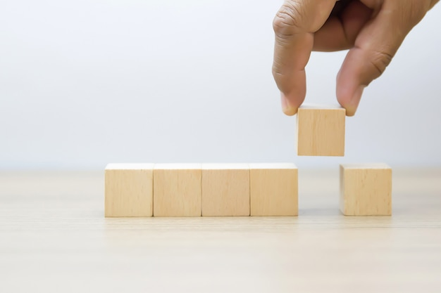 Ręcznie podnosząc drewniany klocek bez grafiki. Premium Zdjęcia