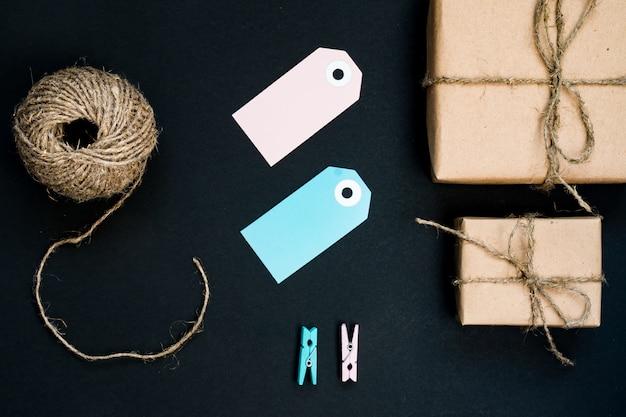 Ręcznie Robione Pudełka Upominkowe Owinięte Papierem Rzemieślniczym Z Niebieską Kartką Papierową, Sznurkiem I Drewnianymi Spinaczami Do Dekoracji. Premium Zdjęcia