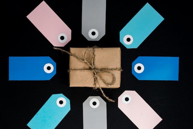 Ręcznie Robione Pudełko Upominkowe Owinięte Papierem Rzemieślniczym, Wokół Którego Znajdują Się Różowe, Szare Etykiety Z Papieru Premium Zdjęcia