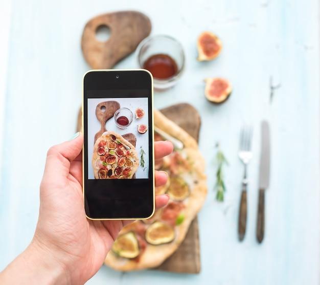 Ręcznie robione zdjęcia na telefon komórkowy: rustykalna domowa pizza z figami, szynką parmeńską i mozzarellą, ciemna drewniana deska do serwowania na jasnoniebieskim tle. widok z góry. Premium Zdjęcia