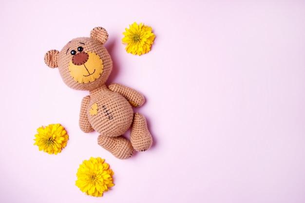 Ręcznie Robiony Miś Amigurumi Z żółtą Chryzantemą Odizolowywającą Na Różowym Tle. Tło Dla Dzieci. Skopiuj Miejsce, Widok Z Góry. Premium Zdjęcia