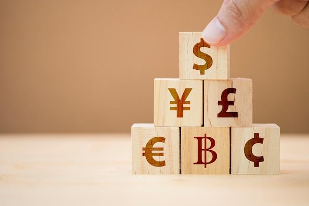 Ręcznie Stawia Drewniany Sześcian Znaku Dolara Amerykańskiego Yuan Yen Euro I Funt Szterling. Premium Zdjęcia
