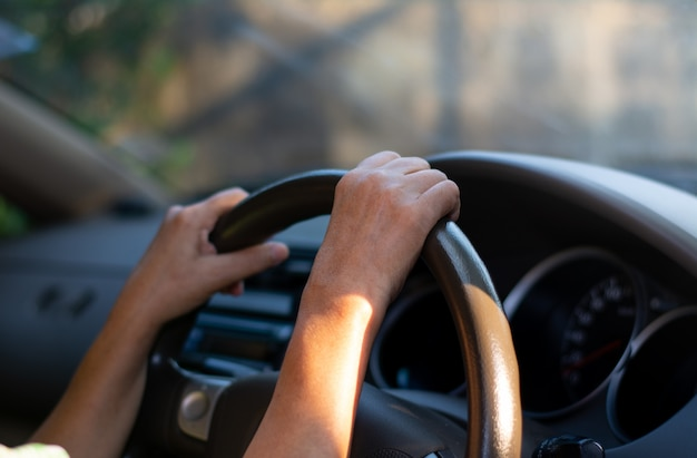Ręcznie trzymana kierownica samochodowa. kobieta ostrożnie jeździ samochodem. Premium Zdjęcia