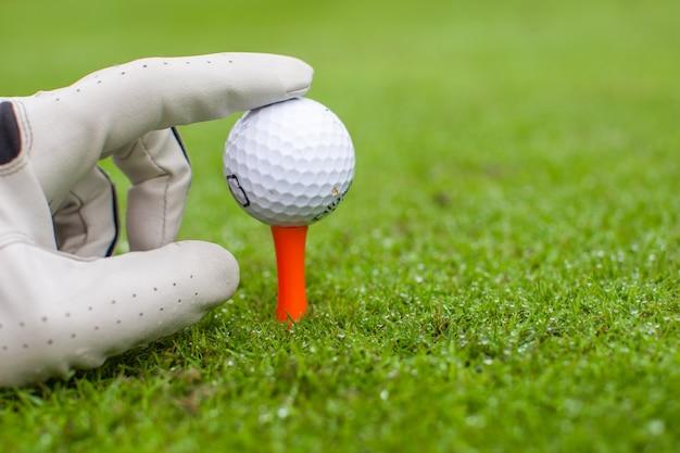 Ręcznie umieść piłkę golfową na tee nad pięknym polem golfowym z zieloną trawą Premium Zdjęcia