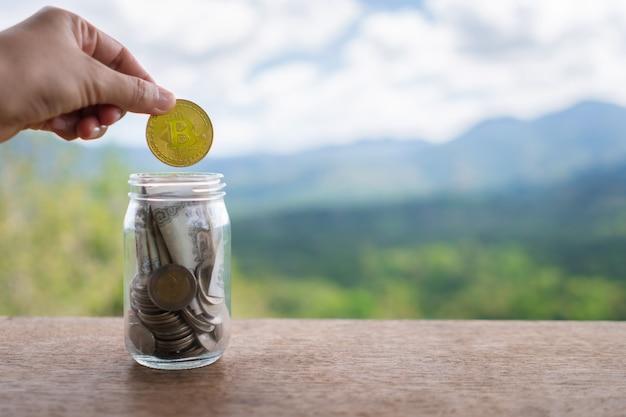 Ręcznie Upuszczaj Złoty Bitcoin W Słoiku Pełnym Monet I Banknotów, Co Oznacza Oszczędność Inwestycji Dzięki Cyfrowej Sieci Kryptowalutowej Sieci Fintech. Technologia Biznesowa. Premium Zdjęcia