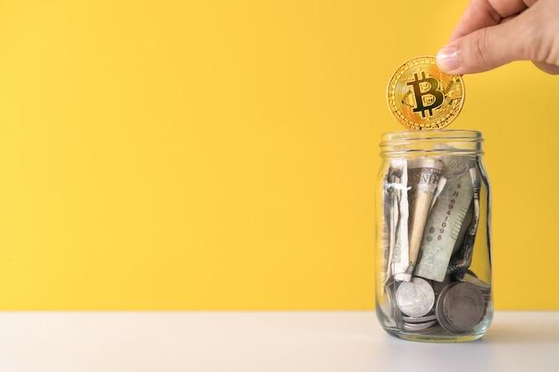 Ręcznie Upuszczaj Złoty Bitcoin W Słoiku Pełnym Monet I Banknotów, Co Oznacza Oszczędność Inwestycji Dzięki Cyfrowej Sieci Kryptowalutowej Sieci Fintech. Premium Zdjęcia