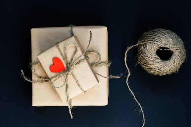 Ręcznie Wykonane Pudełko Prezentowe Owinięte Papierem Rzemieślniczym Z Czerwonym Drewnianym Sercem, Liną I Kokardą Na Czarnym Tle Premium Zdjęcia