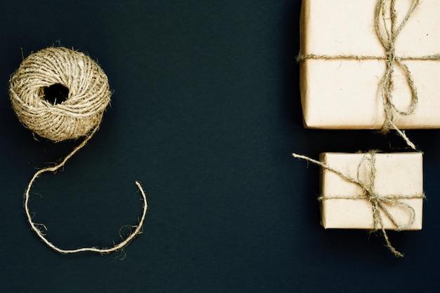 Ręcznie Wykonane Pudełko Zapakowane W Papier Rzemieślniczy Z Czerwonym Drewnianym Sercem, Liną I Kokardą Na Czarnym Tle. Widok Z Góry, Leżał Płasko Premium Zdjęcia