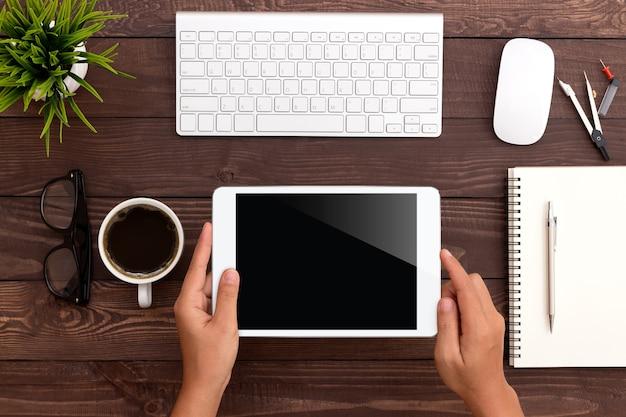 Ręcznie Za Pomocą Białego Tabletu Na Obszarze Roboczym Premium Zdjęcia