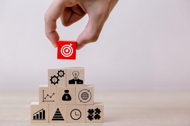 Ręcznie zamknij ręce biznesmenów, układając drewniane klocki w kroki Premium Zdjęcia