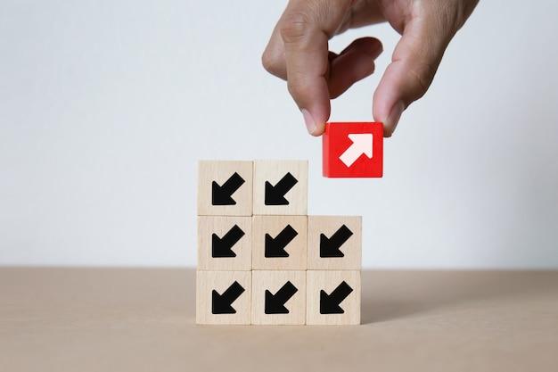 Ręcznie, Zbierając Czerwony Symbol Strzałki Na Drewnianym Bloku Zabawki. Premium Zdjęcia