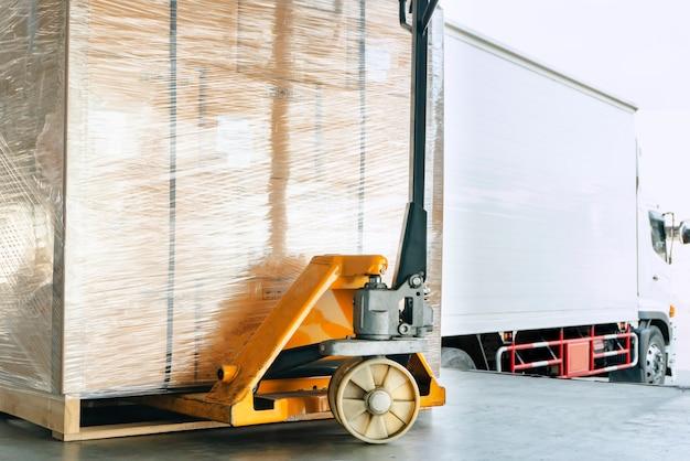 Ręczny wózek paletowy lub podnośnik paletowy z przesyłką kurierską na palecie. Premium Zdjęcia