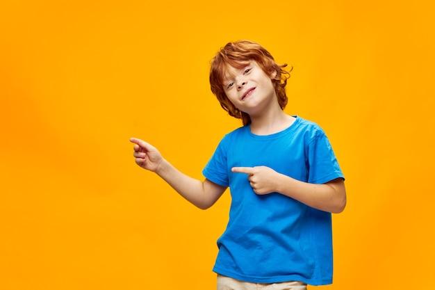 Redheaded Boy Niebieski T-shirt żółte Tło Piegi I Wolna Przestrzeń, Wskaż Palcem W Bok Premium Zdjęcia