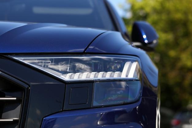 Reflektory i zderzak drogiego współczesnego pojazdu na parkingu miejskim na zewnątrz Premium Zdjęcia