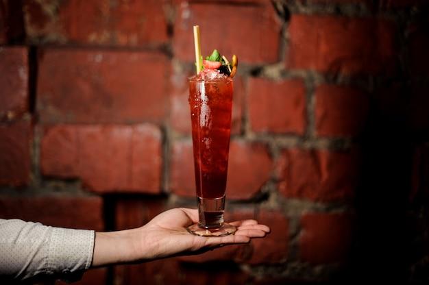 Ręka barmana trzyma szklankę świeżego letniego koktajlu szewcowego ozdobionego truskawką i miętą Premium Zdjęcia