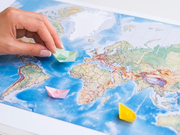 Ręka bawi się papierowymi łodziami na mapie Darmowe Zdjęcia