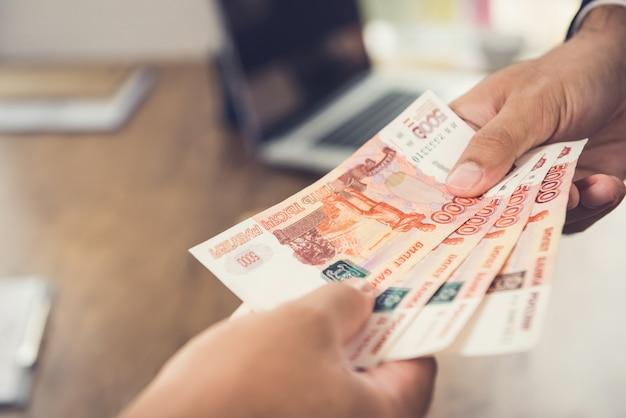 Ręka biznesmen daje pieniądze swojemu partnerowi w walucie rub Premium Zdjęcia